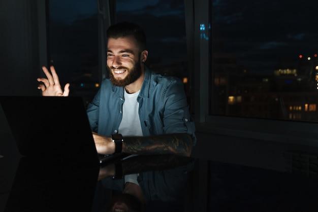 Uśmiechnięty młody mężczyzna pracujący na laptopie siedząc przy stole w pomieszczeniu w nocy, machający ręką