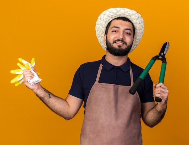 Uśmiechnięty młody mężczyzna rasy kaukaskiej ogrodnik w kapeluszu ogrodniczym, trzymający nożyczki ogrodnicze i rękawiczki odizolowane na pomarańczowej ścianie z miejscem na kopię
