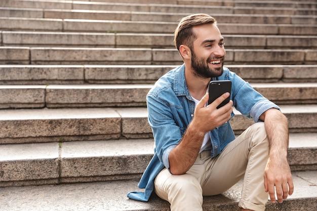 Uśmiechnięty młody mężczyzna siedzący na schodach na zewnątrz, używający telefonu komórkowego