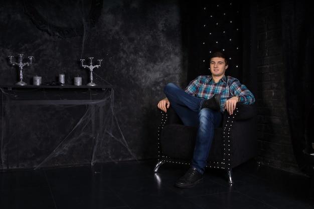Uśmiechnięty młody mężczyzna siedzący ze skrzyżowanymi nogami w pluszowym czarnym krześle z wysokim oparciem w niesamowitym otoczeniu nawiedzonego domu z pajęczynami
