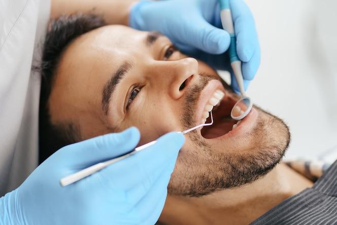 Uśmiechnięty młody mężczyzna siedzi na fotelu dentysty, podczas gdy lekarz bada jego zęby