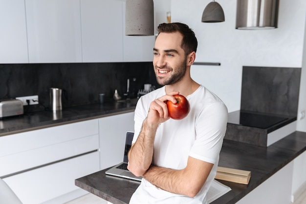 Uśmiechnięty młody mężczyzna trzyma jabłko stojąc w kuchni w domu