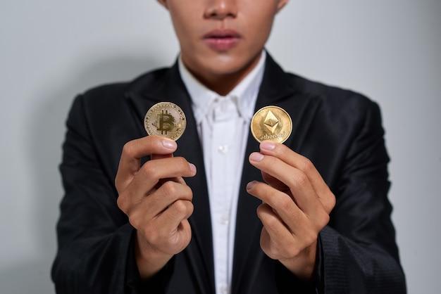 Uśmiechnięty młody mężczyzna ubrany w koszulę i kurtkę pokazujący dwa złote bitcoiny odizolowane na szarym tle
