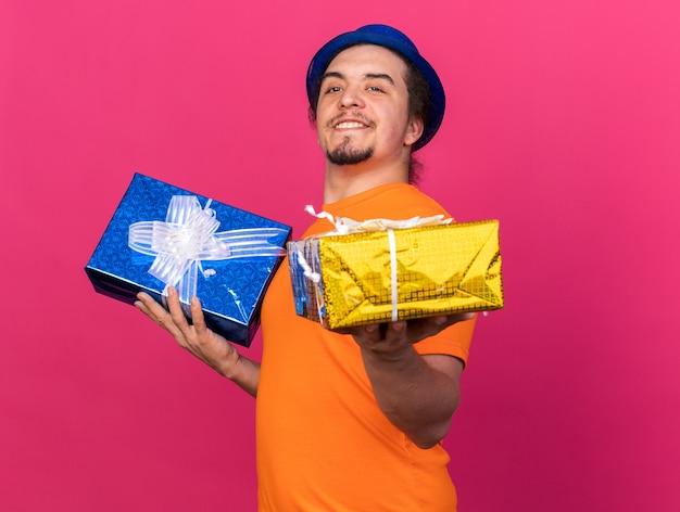 Uśmiechnięty młody mężczyzna w imprezowym kapeluszu trzymającym pudełka na prezenty przed kamerą