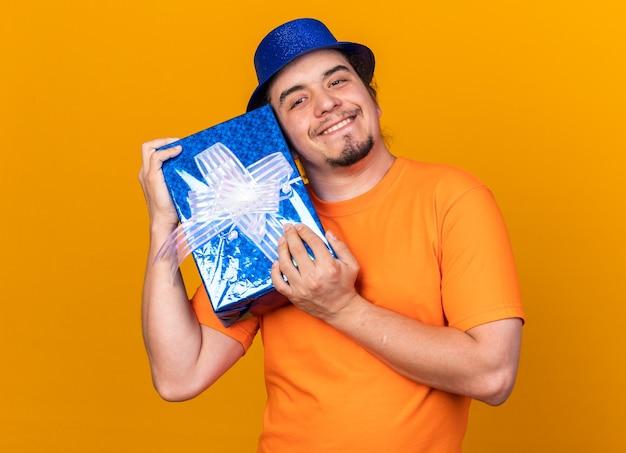 Uśmiechnięty młody mężczyzna w kapeluszu imprezowym, trzymający pudełko na prezent na pomarańczowej ścianie