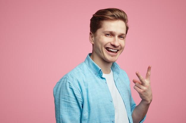 Uśmiechnięty młody mężczyzna w niebieskiej koszuli i gestykuluje vsign przez różową ścianę