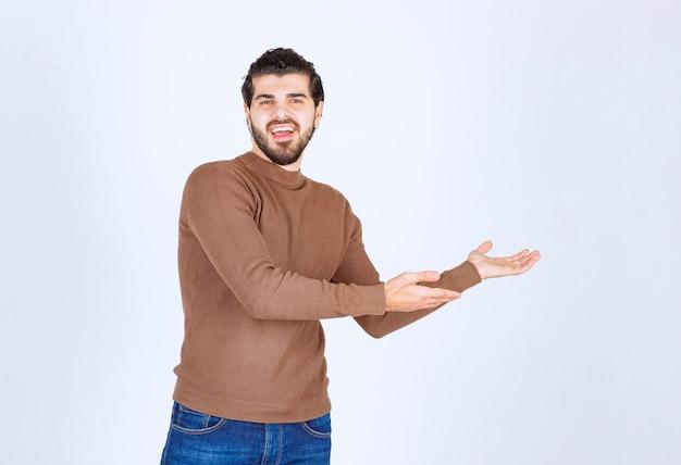 Uśmiechnięty młody model człowieka stojącego i pokazującego ręce. zdjęcie wysokiej jakości