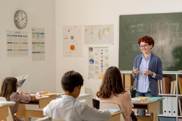 Uśmiechnięty młody nauczyciel stojący przed uczniami z tablicą z tyłu