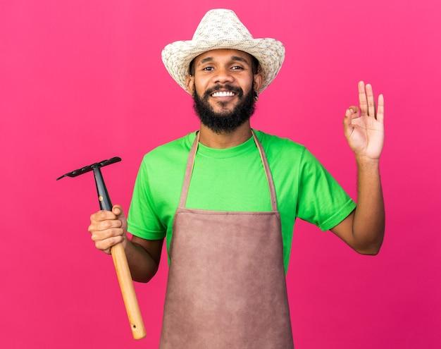 Uśmiechnięty młody ogrodnik afro-amerykański facet w kapeluszu ogrodniczym, trzymający grabie, pokazując w porządku gest, odizolowany na różowej ścianie