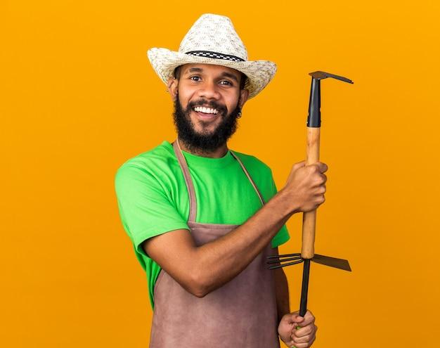 Uśmiechnięty młody ogrodnik afroamerykański facet ubrany w kapelusz ogrodniczy, trzymający grabie z motyką na białym tle na pomarańczowej ścianie