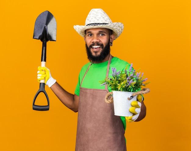 Uśmiechnięty młody ogrodnik afroamerykański facet w kapeluszu ogrodniczym i rękawiczkach, trzymający łopatę z kwiatem w doniczce na białym tle na pomarańczowej ścianie