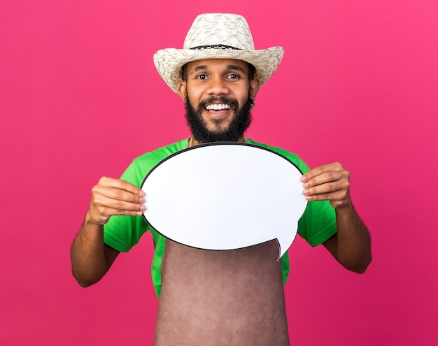 Uśmiechnięty młody ogrodnik afroamerykański facet w kapeluszu ogrodniczym, trzymający dymek