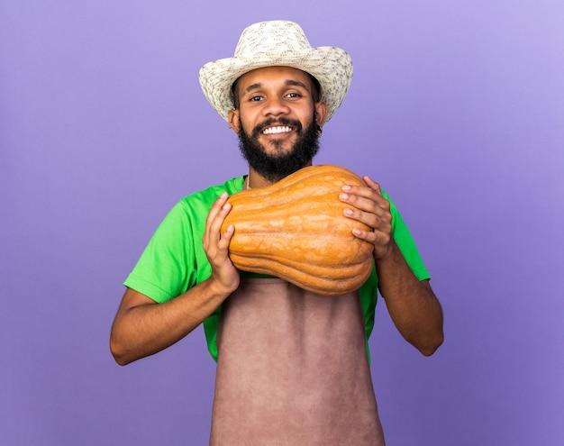Uśmiechnięty młody ogrodnik afroamerykański facet w kapeluszu ogrodniczym trzymający dynię