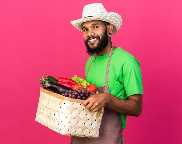 Uśmiechnięty młody ogrodnik afroamerykański facet w kapeluszu ogrodniczym, trzymający kosz warzyw na białym tle na różowej ścianie
