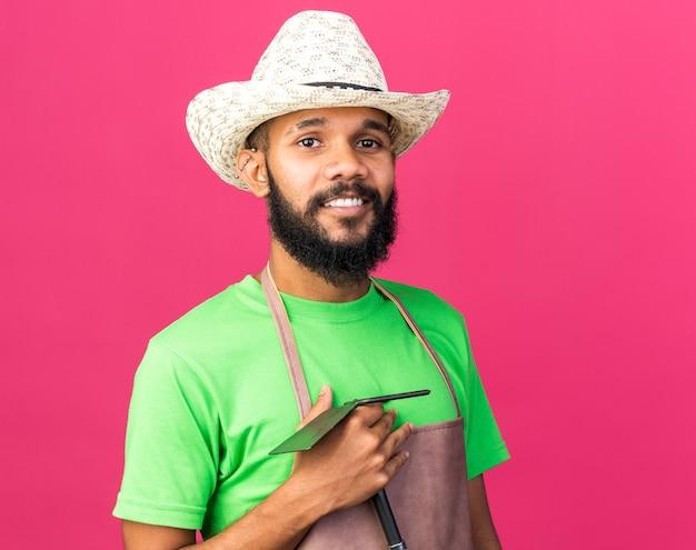 Uśmiechnięty młody ogrodnik afroamerykański facet w kapeluszu ogrodniczym, trzymający motykę na białym tle na różowej ścianie