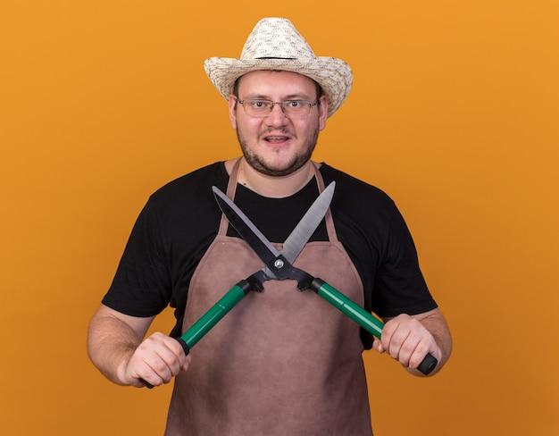 Uśmiechnięty młody ogrodnik męski na sobie kapelusz ogrodniczy i rękawiczki, trzymając maszynki do strzyżenia na białym tle na pomarańczowej ścianie