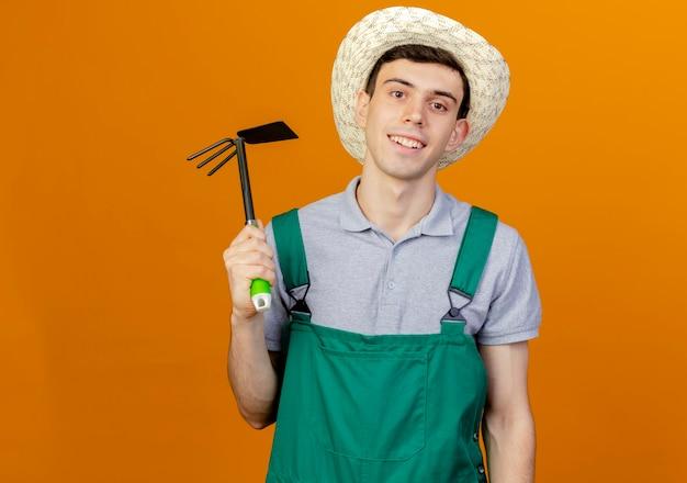 Uśmiechnięty młody ogrodnik męski na sobie kapelusz ogrodniczy posiada grabie motyka
