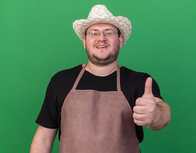 Uśmiechnięty młody ogrodnik mężczyzna na sobie kapelusz ogrodniczy pokazując kciuk do góry na białym tle na zielonej ścianie