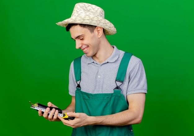 Uśmiechnięty młody ogrodnik mężczyzna ubrany w kapelusz ogrodniczy mierzy bakłażana z centymetrem