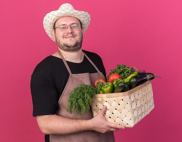 Uśmiechnięty młody ogrodnik mężczyzna w kapeluszu ogrodnictwo trzymając kosz warzyw na białym tle na różowej ścianie