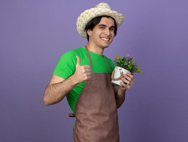 Uśmiechnięty młody ogrodnik mężczyzna w mundurze na sobie kapelusz ogrodniczy trzyma kwiat w doniczce pokazując kciuk do góry
