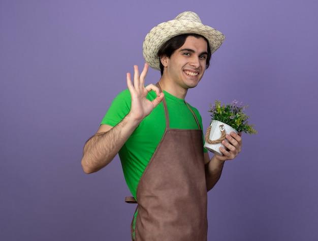 Uśmiechnięty młody ogrodnik mężczyzna w mundurze na sobie kapelusz ogrodniczy trzyma kwiat w doniczce, pokazując w porządku gest