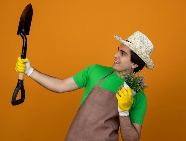 Uśmiechnięty młody ogrodnik mężczyzna w mundurze na sobie kapelusz ogrodniczy z rękawiczkami, trzymając kwiat w doniczce i podnosząc i patrząc na pik