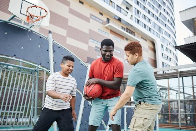 Uśmiechnięty młody ojciec grający w koszykówkę z synami i ukrywający przed nimi piłkę na miejskim boisku sportowym