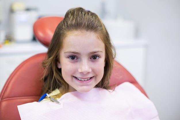 Uśmiechnięty młody pacjent siedzi na krześle dentystów