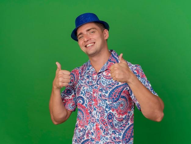 Uśmiechnięty młody partyjny facet na sobie niebieski kapelusz pokazujący kciuki do góry na białym tle na zielono