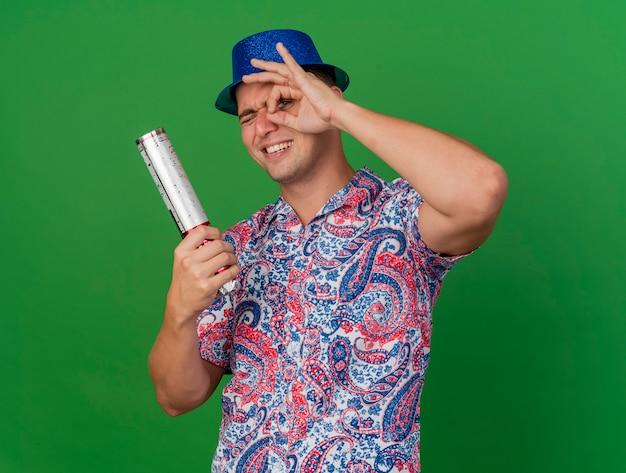 Uśmiechnięty młody partyjny facet na sobie niebieski kapelusz trzymając armatę konfetti pokazujący wygląd gest na białym tle na zielono