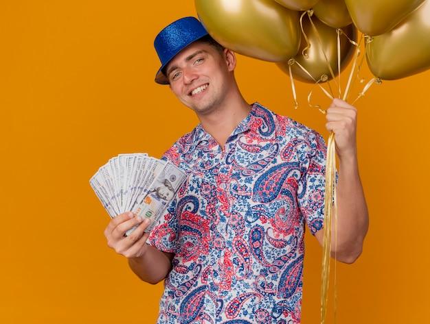 Uśmiechnięty młody partyjny facet na sobie niebieski kapelusz trzymając balony z pieniędzmi odizolowane na pomarańczowo