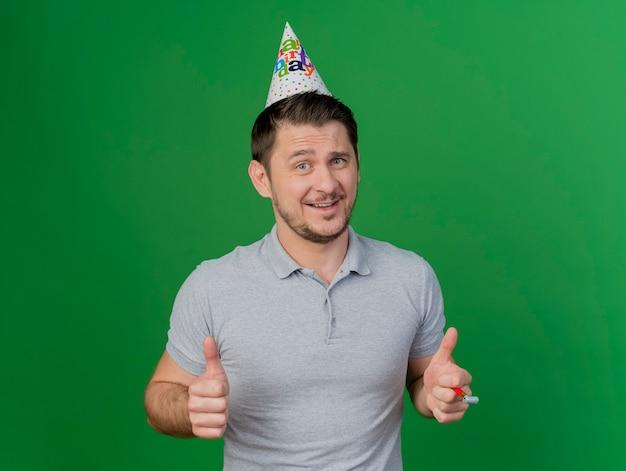 Uśmiechnięty młody partyjny facet ubrany w czapkę urodziny trzymając gwizdek pokazując kciuki do góry na białym tle na zielono