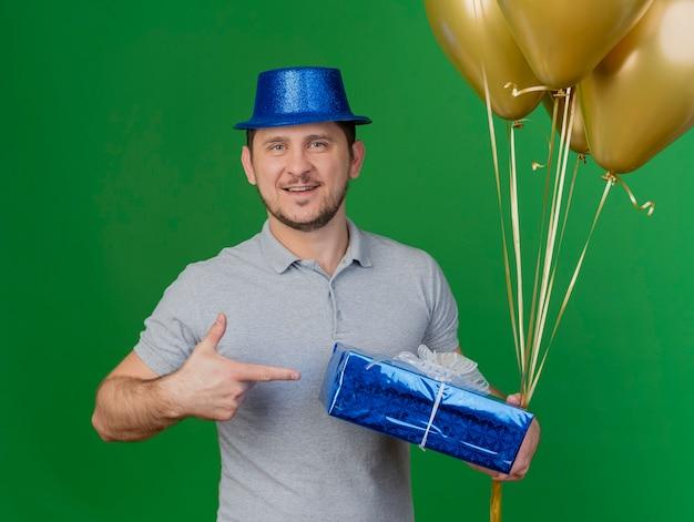Uśmiechnięty młody partyjny facet ubrany w kapelusz partii gospodarstwa i wskazuje na pudełko z balonami na białym tle na zielono