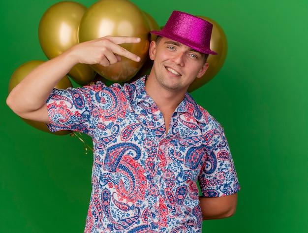 Uśmiechnięty młody partyjny facet ubrany w różowy kapelusz stojący przed balonami i pokazujący gest pokoju na zielono