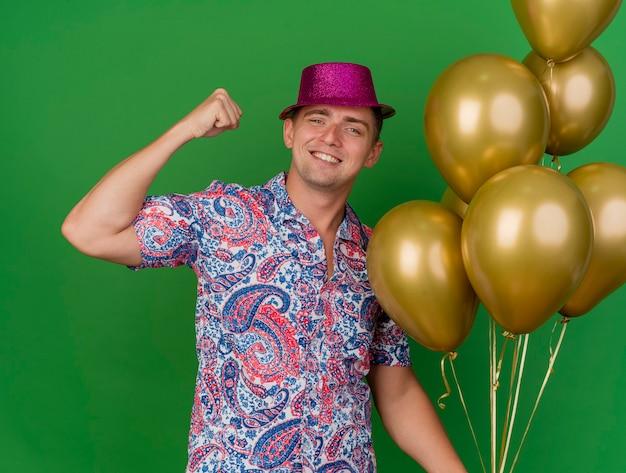 Uśmiechnięty młody partyjny facet ubrany w różowy kapelusz trzymając balony i pokazując silny gest odizolowany na zielono