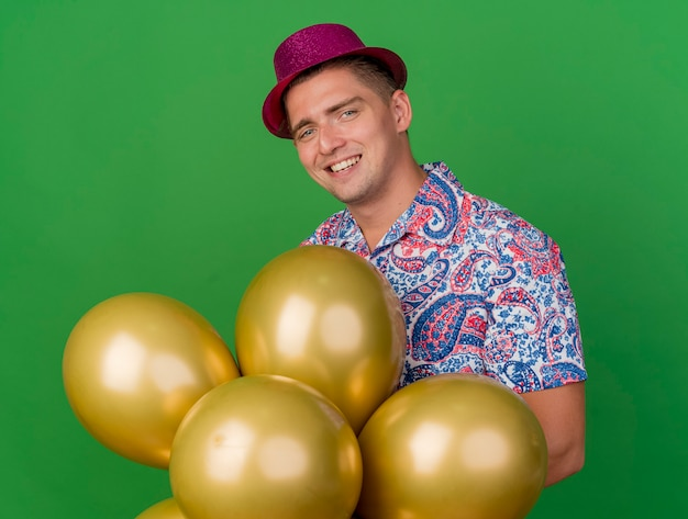 Uśmiechnięty młody partyjny facet ubrany w różowy kapelusz trzymając balony na białym tle na zielono