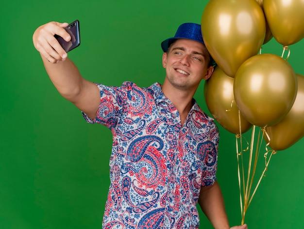 Uśmiechnięty młody partyjny facet w niebieskim kapeluszu trzymając balony i weź selfie na zielono