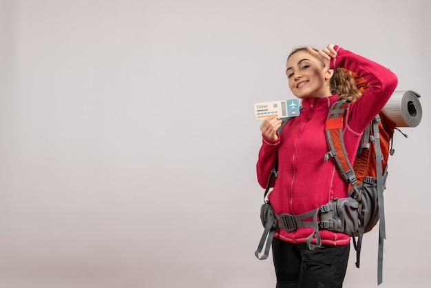 Uśmiechnięty młody podróżnik z dużym plecakiem trzymającym bilet podróżny na szaro