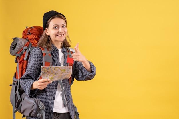 Uśmiechnięty młody podróżnik z plecakiem trzymającym mapę wskazującą na aparat