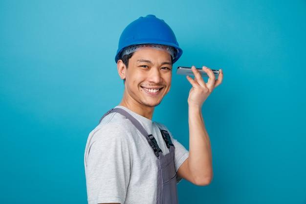 Uśmiechnięty młody pracownik budowlany na sobie hełm ochronny i mundur stojący w widoku profilu trzymając telefon komórkowy w pobliżu ucha