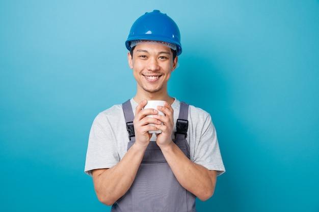 Uśmiechnięty młody pracownik budowlany na sobie hełm ochronny i mundur trzymając filiżankę herbaty obiema rękami