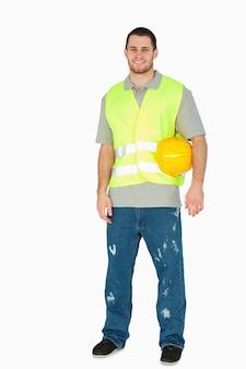 Uśmiechnięty młody pracownik budowlany niesie jego hełm pod jego ręką