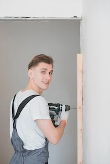 Uśmiechnięty młody pracujący mężczyzna w kombinezonie musztruje śruby z elektrycznym śrubokrętem w mieszkaniu