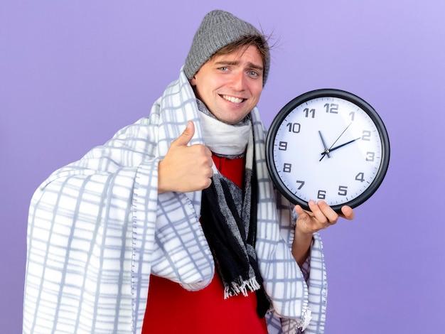 Uśmiechnięty młody przystojny blondyn chory w czapce zimowej i szaliku owiniętym w kratę, trzymając zegar patrząc na kamerę, pokazując kciuk w górę na białym tle na fioletowym tle