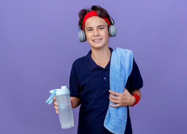 Uśmiechnięty młody przystojny chłopak sportowy sobie opaskę i opaski na rękę i słuchawki z szelki dentystyczne i ręcznik na ramieniu, trzymając butelkę wody na białym tle