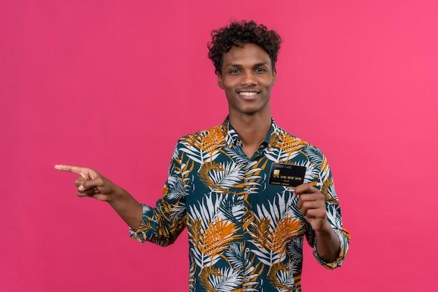 Uśmiechnięty młody przystojny ciemnoskóry mężczyzna z kręconymi włosami w koszulce z nadrukiem liści patrząc na kamery, pokazując kartę kredytową i wskazując palcem wskazującym na różowym tle