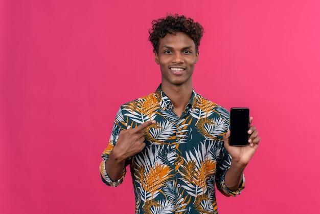 Uśmiechnięty młody przystojny ciemnoskóry mężczyzna z kręconymi włosami w koszuli z nadrukiem liści, wskazując na telefon komórkowy z palcem wskazującym na różowym tle