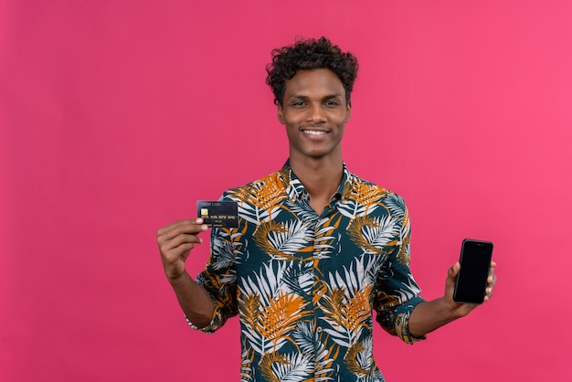 Uśmiechnięty młody przystojny ciemnoskóry mężczyzna z kręconymi włosami w liściach drukowanej koszuli pokazujący pusty ekran smartfona z kartą kredytową na różowym tle