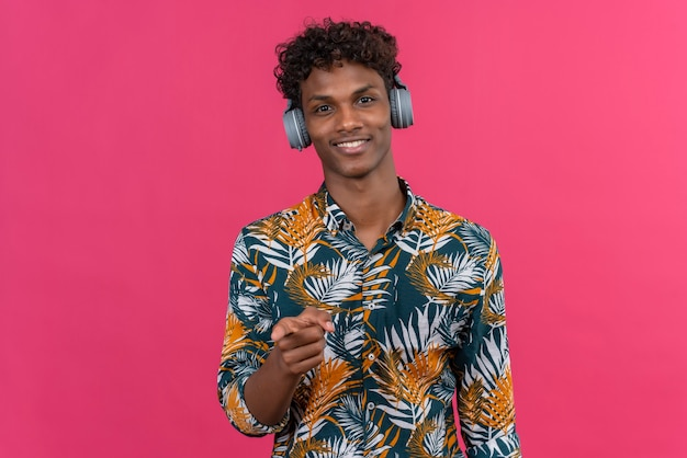 Uśmiechnięty młody przystojny ciemnoskóry mężczyzna z kręconymi włosami w liściach koszulę z nadrukiem w słuchawkach, wskazując palcem wskazującym na aparat na różowym tle